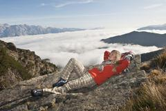 Austria, Steiermark, Reiteralm, Female mountain hiker resting on rock - stock photo