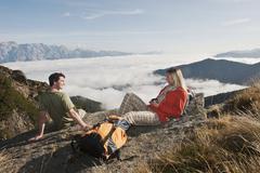 Austria, Steiermark, Reiteralm, Hikers resting on rock, woman holding cup Stock Photos