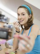 Young woman applying lipstick Stock Photos