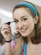 Stock Photo of young woman applying mascara