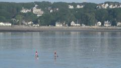 Two paddle boarders near shore, dawn, Atlantic, New England houses Stock Footage