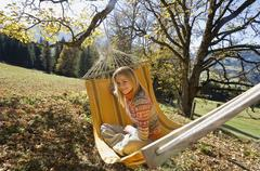 Austria, Salzburger Land, Altenmarkt, Woman sitting in hammock, smiling Stock Photos