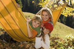 Austria, Salzburger Land, Altenmarkt, Mother and children lying in hammock, - stock photo