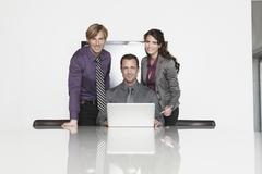 Stock Photo of Germany, Cologne, Three Business people in office using laptop