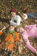 Austria, Salzburger Land, Altenmarkt, Mother and children lying on autumn - stock photo