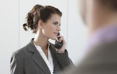 Germany, Cologne, Businesswoman using phone, looking away Stock Photos