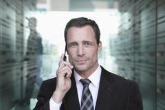 Stock Photo of Germany, Cologne, Businessman standing in corridor, using mobile phone,