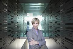 Stock Photo of Germany, Cologne, Businessman in corridor, arms crossed, portrait
