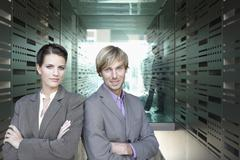 Stock Photo of Germany, Cologne, Business people standing in corridor, arms crossed, portrait