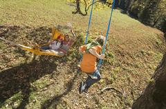 Austria, Salzburger Land, Altenmarkt, Mother watching son (8-9) playing on swing - stock photo