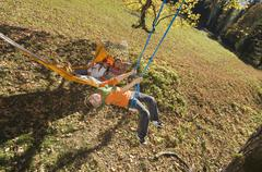 Austria, Salzburger Land, Altenmarkt, Mother watching son (8-9) playing on swing Stock Photos
