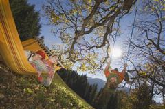 Austria, Salzburger Land, Altenmarkt, Mother watching son (8-9) playing on swing Stock Photos