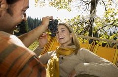 Austria, Salzburger Land, Altenmarkt, Couple lying in hammock, smiling, portrait - stock photo