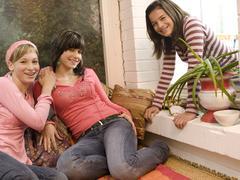 Girl friends at home, looking at camera, smiling Stock Photos