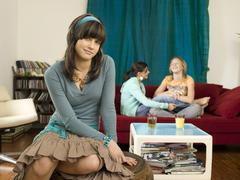 Girl sitting on stool, friends in background Stock Photos