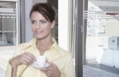 Germany, Cologne, Businesswoman in office taking a break, drinking coffee Stock Photos