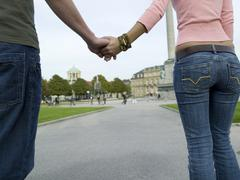 germany; stuttgart, couple walking hand in hand, rear biew - stock photo