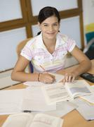 young woman sitting on desk, writing - stock photo