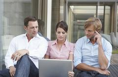 Germany, Cologne, Three business people sitting side by side, using laptop - stock photo
