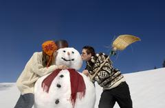 Young couple kissing snow man, low angle view Stock Photos