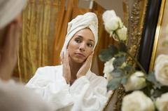 Young woman wearing towel on head, portrait - stock photo