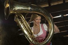 Young woman in traditional costume, holding a tuba, portrait - stock photo