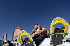 Young couple sitting in snow with snow shoes, low angle view - stock photo