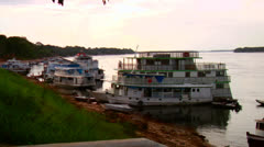 River boats line the waterway on the Amazon River in Brazil. - stock footage