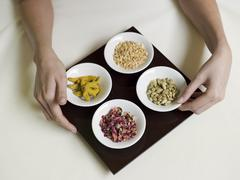Woman with spice in bowls on bed, elevated view - stock photo