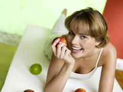 Stock Photo of Woman lying on bed with apples, smiling
