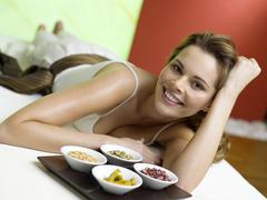 Woman lying on bed with spice in bowls, smiling - stock photo