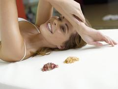 Young woman lying on bed with spice, smiling - stock photo
