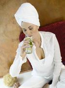 Stock Photo of Woman sitting on cushion, drinking lime water, close-up
