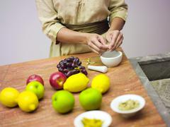 Woman in kitchen with fruits, mid-section - stock photo