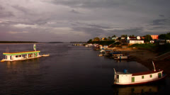 Boats move along the Amazon River near a village. - stock footage