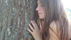 Happy beautiful girl hugging big tree Stock Footage