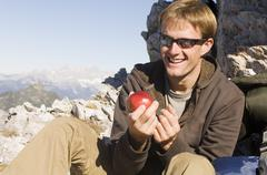 Austria, Salzburg County, Young man holding an apple Stock Photos