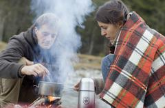 Austria, Salzburg County, Young couple cooking at campfire - stock photo