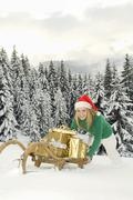 Austria, Salzburger Land, Altenmarkt, Young woman pushing sledge with Christmas - stock photo