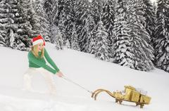 Austria, Salzburger Land, Altenmarkt, Young woman pulling sledge with Christmas Stock Photos
