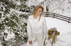 Austria, Salzburger Land, Young woman pulling sledge with Christmas presents - stock photo