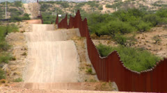 The U.S. Mexico border fence becomes a focal point for immigration issues. - stock footage