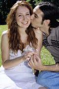 Young man kissing young woman in garden, close-up - stock photo