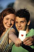 Young couple showing ace of hearts, focus on couple at background, close-up Stock Photos