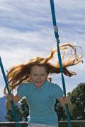 Germany, Salzburger Land, Girl (8-9) on swing - stock photo