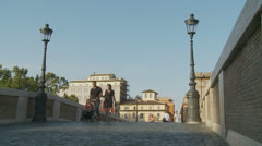 Young couple with push chair, over Roman bridge (slomo dolly) Stock Footage