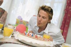 Man blowing candle on torte, portrait Stock Photos