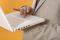 Stock Photo of Businessman using laptop, middle section, close up