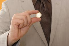 Stock Photo of Man holding Euro coin, middle section, close up