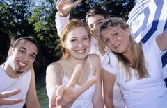 Four young people showing victory sign, close-up, portrait Stock Photos